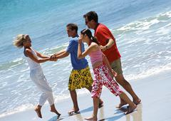 Family walking together on the beach. Stock Photos