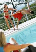 Woman watching teenage girl push teenage boy into pool. Stock Photos