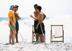 People standing on beach - stock photo