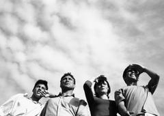 Four adults looking, low angle view, b&w Stock Photos