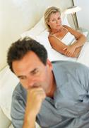 Couple in bed, woman with arms folded, man holding head Stock Photos