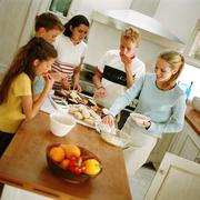 Young people snacking around table in kitchen Stock Photos