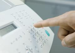 Man's finger about to push button on fax machine Stock Photos