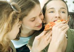 Three preteen girls, feeding friend pizza - stock photo