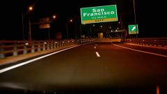Driving on highway/interstate at night,  exit sign of the city of san francis Stock Footage
