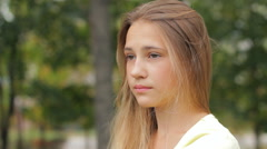 Stock Video Footage of Young Girl In City Park Sad Serious Concerned Worried Face Portrait HD