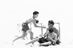 Man roughhousing on beach with teenage sons, black and white - stock photo