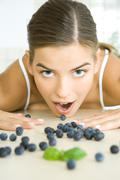 Fresh blueberries scattered across counter, young woman opening mouth to eat one - stock photo