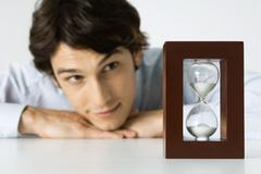 Man looking at hourglass, head resting on hands - stock photo