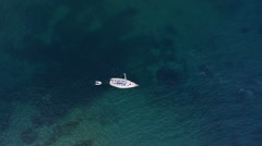 Aerial - Flight over the sailing boat on clear blue water, leaving marina Stock Footage