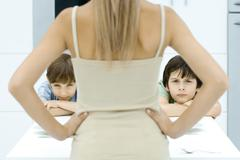 Boys pouting at kitchen table, being disciplined by mother, rear view Stock Photos
