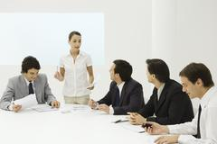 Businesswoman addressing male colleagues at conference table Stock Photos