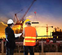Engineering man working in building construction site with worker foreman aga Stock Photos