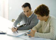 Man helping teenage son with homework Stock Photos