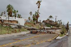 broken by hurricane electric wooden post - stock photo