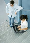 Two colleagues talking, one sitting on stairs with laptop - stock photo