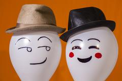 balloon characters wearing hats and smiling - stock photo