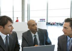 Three businessmen talking in airport Stock Photos