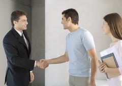 Couple greeting salesman Stock Photos