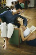 Pregnant woman sitting on floor with book, leaning back against husband and Stock Photos