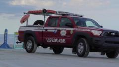 Lifeguard truck driving on beach Stock Footage