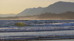 Surfers at Wickaninnish Beach in Pacific Rim National Park Stock Footage