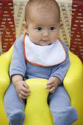 Baby sitting on booster seat, portrait Stock Photos