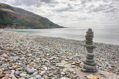 stones balancing on top of each to make a tower on a beach - stock photo