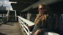 Young woman with sunglasses standing on pier by the sea Stock Footage