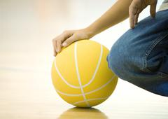 Teen boy crouching, holding basketball, close-up of hand on ball and knee Stock Photos
