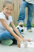 Girl sitting on driveway, painting, boy with foot on soccerball in background - stock photo