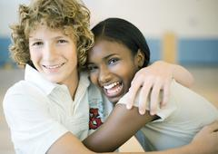 Teen couple sitting with arms around each other Stock Photos
