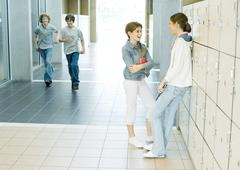 Two teen girls talking by lockers while boys run through hallway - stock photo
