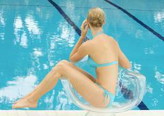 Woman in bikini sitting by pool in transparent chair - stock photo