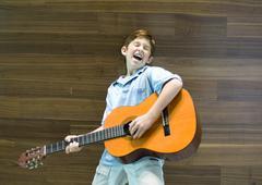 Boy playing guitar and singing Kuvituskuvat