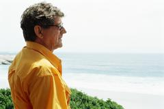 Man at the beach, looking at view, side view Stock Photos