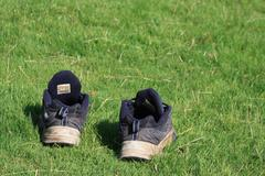 Pair of blue trainers on green grass Stock Photos