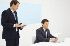 Two businessmen in office looking down at laptop computer together, one holding - stock photo