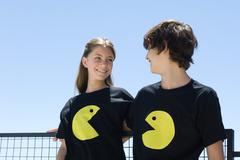 Young couple wearing tee-shirts printed with graphic characters, smiling at each Kuvituskuvat