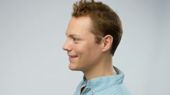 Young adult man turns his head, looks to the camera and smiles Stock Footage