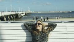 Young happy woman enjoying beautiful weather on the beach during autumn season Stock Footage