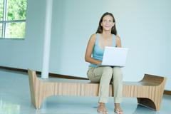 Teen girl sitting on bench, using laptop computer, smiling, looking up - stock photo