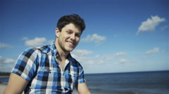 Handsome young man in casual checkered shirt against bright beach background Stock Footage