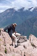 Stock Photo of tourist sends status in social networks, sitting over the precipice of colca