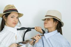 Two young female friends dressed in hats, pulling each other's ties, one Stock Photos