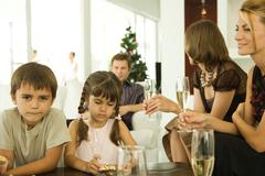 Two children holding Christmas ornaments, adults drinking champagne - stock photo