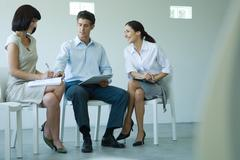 Three business associates sitting on chairs, holding documents on laps, talking - stock photo