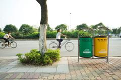 China, Guangdong Province, Guangzhou, cyclists riding in street behind recycling - stock photo