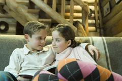 Preteen boy and girl with book, smiling at each other - stock photo