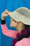 Teenage girl pulling sun hat over eyes, side view, portrait Stock Photos